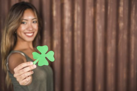 happy-woman-holding-green-paper-clover_23-2148075114